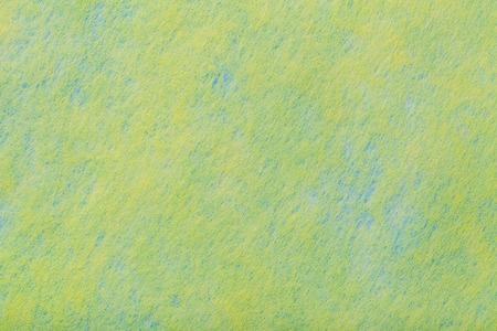 Construction of a light green background with blue spots of felt fabric, closeup. Texture of woolen matt yellow textile. Cloth backdrop.
