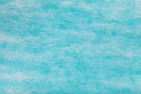 Construction of a light blue background with white spots of felt fabric, closeup. Texture of woolen matt textile. Cloth backdrop.