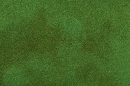 Dark green matte background of suede fabric, closeup. Velvet texture of seamless emerald leather. Felt material macro.