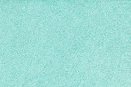 Light turquoise matte background of suede fabric, closeup. Velvet texture of seamless green woolen felt.