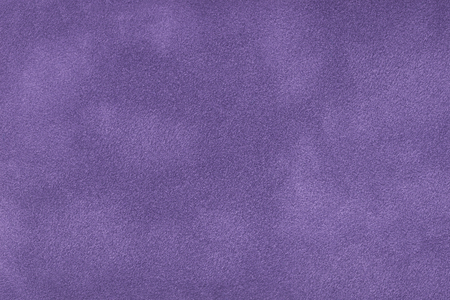 Dark violet matte background of suede fabric, closeup. Velvet texture of seamless purple leather. Felt material macro.