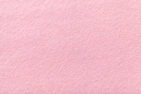 Light pink matte background of suede fabric, closeup. Velvet texture of seamless rose woolen felt. Banque d'images
