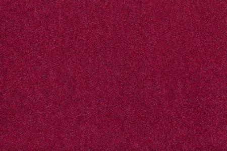 Dark red matte background of suede fabric, closeup. Velvet texture of seamless wine woolen felt. Stock Photo