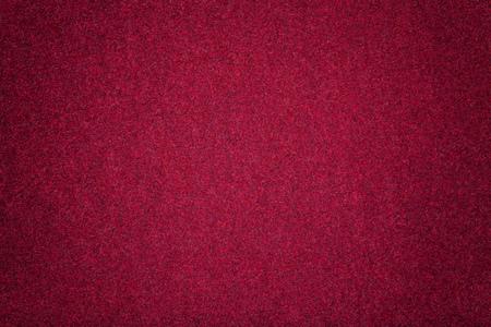 Dark red matte background of suede fabric, closeup. Velvet texture of seamless wine woolen felt with vignette.
