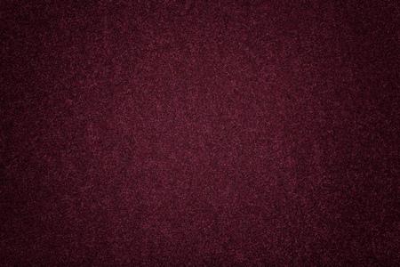 Dark purple matte background of suede fabric, closeup. Velvet texture of seamless wine woolen felt with vignette.
