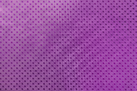 Dark purple background from metal foil paper with a pattern of sparkling stars closeup. Texture of lilac metallized wrapping holiday paper surface.