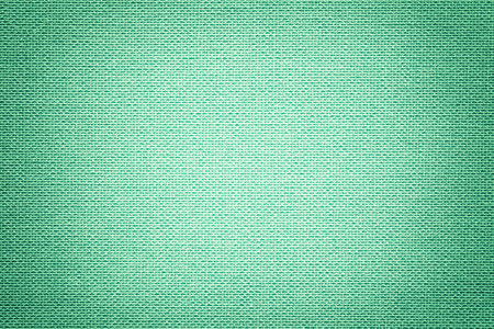 Light green background from a textile material with wicker pattern, closeup. Structure of the turquoise fabric with texture. Cloth cyan backdrop with vignette.