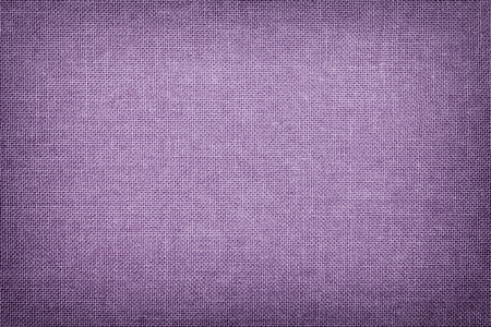 Dark violet background from a textile material with wicker pattern, closeup. Structure of the light lilac fabric with texture. Cloth lavender backdrop with vignette.