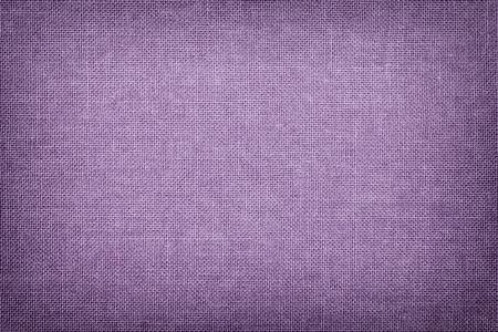 Dunkelvioletter Hintergrund aus Textilmaterial mit Korbmuster, Nahaufnahme. Struktur des helllila Stoffs mit Textur. Stofflavendelhintergrund mit Vignette.