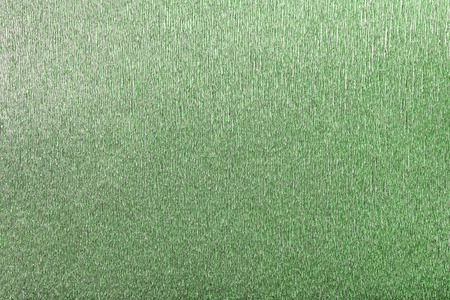 Textural of green foil background of wavy corrugated paper, closeup. Structure of metallic wrinkled crepe dark olive cardboard macro.