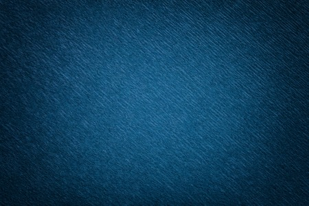 Textural of navy blue background of wavy corrugated paper, closeup. Structure of wrinkled crepe dark denim cardboard with vignette.