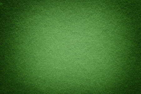 Texture of old olive paper background, closeup. Structure of dense dark green kraft cardboard. Felt gradient backdrop closeup.