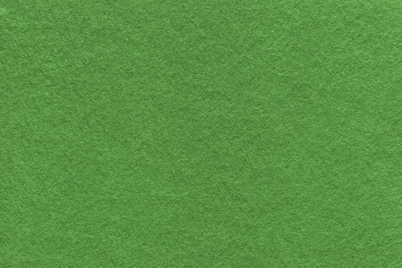 Texture of old dark green paper background, closeup. Structure of dense moss cardboard.