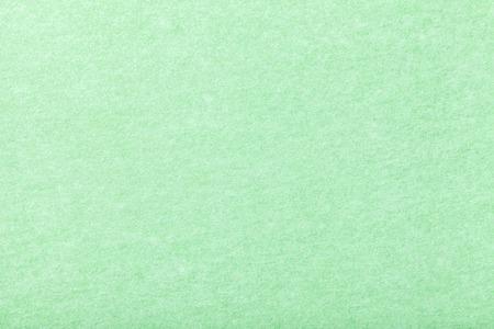 Light green matte background of suede fabric, closeup. Velvet texture of seamless mint woolen felt. Stock Photo