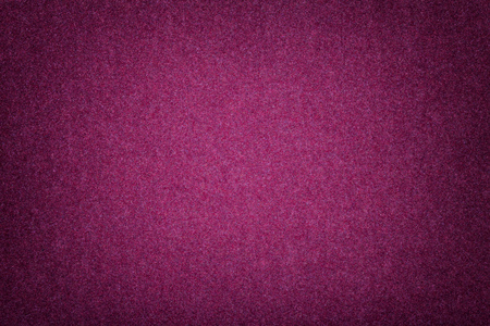 Dark purple matte background of suede fabric, closeup. Velvet texture of seamless wine woolen felt with vignette.