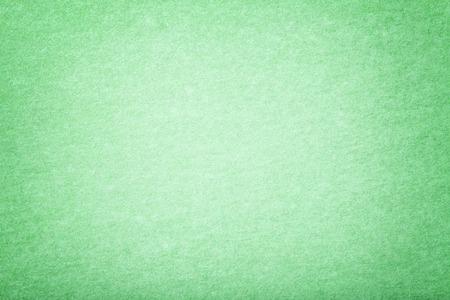 Light green matte background of suede fabric, closeup. Velvet texture of seamless mint woolen felt with vignette.