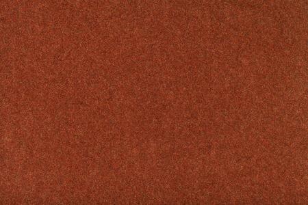 Dark orange matte background of suede fabric, closeup. Velvet texture of seamless red woolen felt. Stock Photo