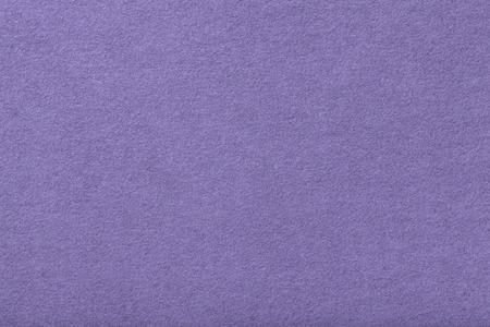 Light purple matte background of suede fabric, closeup. Velvet texture of seamless violet woolen felt. Stock Photo