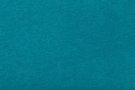Dark turquoise matte background of suede fabric, closeup. Velvet texture of seamless cyan woolen felt.