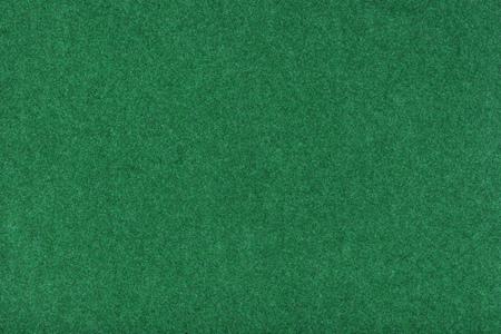 Light green matte background of suede fabric, closeup. Velvet texture of seamless grass woolen felt.