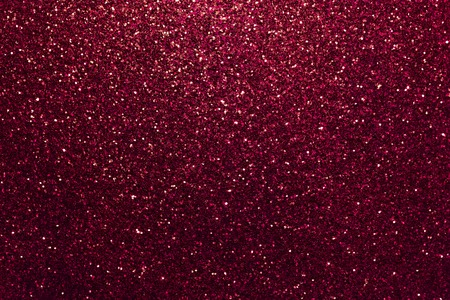 Dark red sparkling background from small sequins, closeup. Brilliant shiny backdrop from textile. Shimmer wine paper