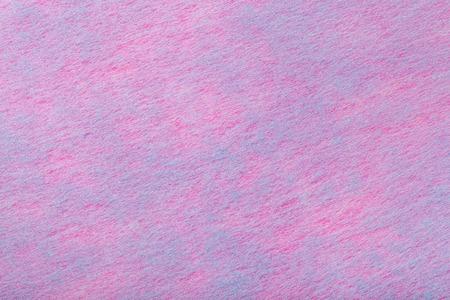 Construction of a light purple background with blue spots of felt fabric, closeup. Texture of fleecy woolen pink matt textile. Cloth backdrop.