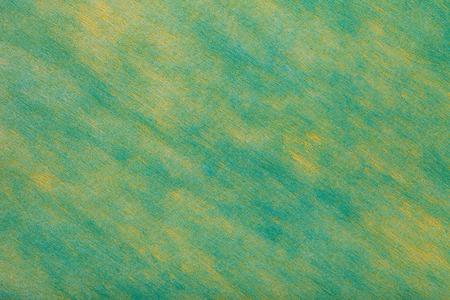 Construction of green turquoise background with light yellow spots of felt fabric, closeup. Texture of woolen fleecy matt textile. Cloth backdrop.