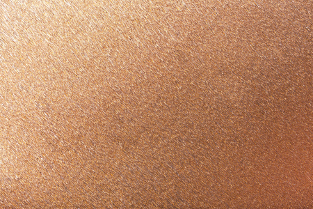 Textural of bronze foil background of wavy corrugated paper, closeup. Structure of metallic wrinkled crepe dark copper cardboard macro.
