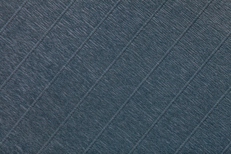Textural of dark gray background of wavy corrugated paper, closeup. Structure of wrinkled crepe black cardboard macro.
