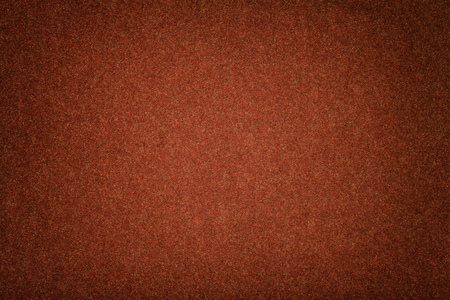 Dark orange matte background of suede fabric, closeup. Velvet texture of seamless brown woolen felt with vignette. Reklamní fotografie