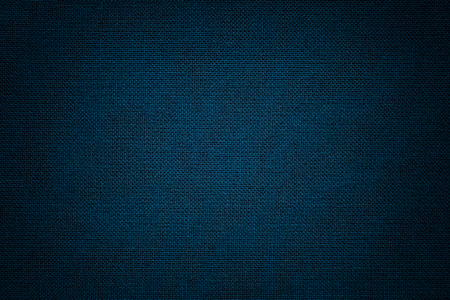 Navy blue background from a textile material with wicker pattern, closeup. Structure of the denim fabric with texture. Cloth backdrop with vignette. Reklamní fotografie
