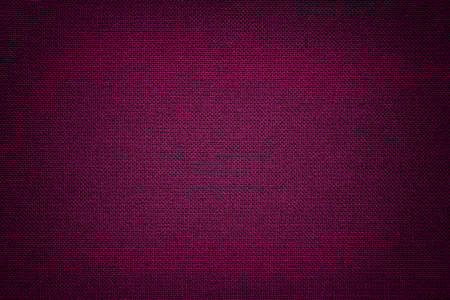 Dark purple background from a textile material with wicker pattern, closeup. Structure of the wine fabric with texture. Cloth backdrop with vignette.