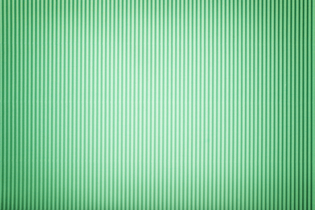 Texture of corrugated light green paper with vignette, macro. Striped pattern of cyan cardboard background, closeup. Reklamní fotografie