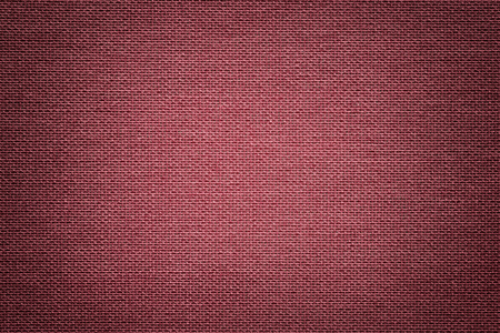 Dark red background from a textile material with wicker pattern, closeup. Structure of the wine fabric with texture. Cloth maroon backdrop with vignette.