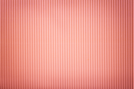 Texture of corrugated dark pink paper with vignette, macro. Striped pattern of gold rose cardboard background, closeup.