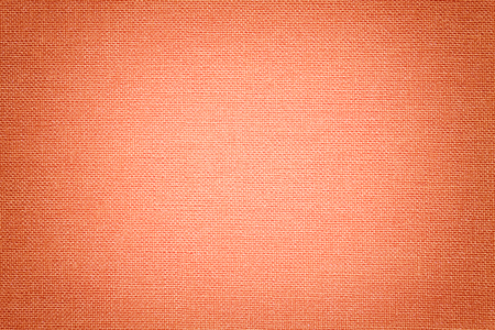 Light coral background from a textile material with wicker pattern, closeup. Structure of the orange fabric with texture. Cloth backdrop with vignette.