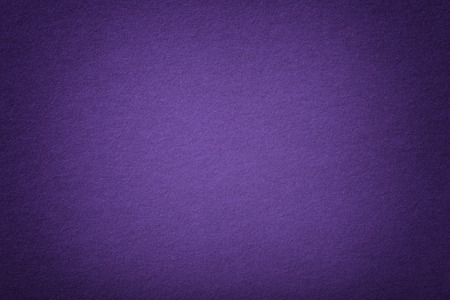 Dark purple matte background of suede fabric, closeup. Velvet texture of seamless violet woolen felt with vignette.