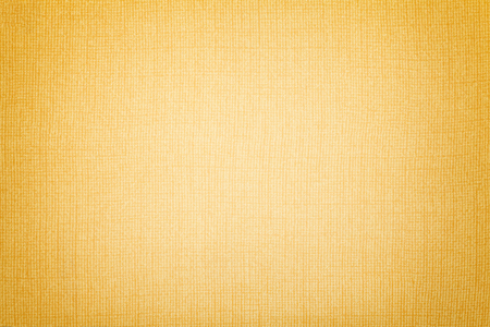 Light yellow background from a textile material with wicker pattern, closeup. Structure of the amber fabric with texture. Cloth golden backdrop with vignette.