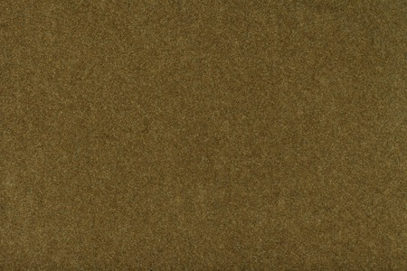 Dark brown matte background of suede fabric, closeup. Velvet texture of seamless khaki woolen felt.