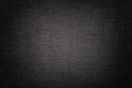 Dark gray background from a textile material with wicker pattern, closeup. Structure of the black fabric with texture. Cloth backdrop with vignette. Reklamní fotografie