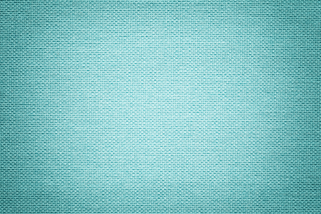 Light blue background from a textile material with wicker pattern, closeup. Structure of the sky fabric with texture. Cloth backdrop with vignette. Reklamní fotografie
