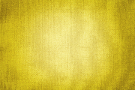 Bright yellow background from a textile material with wicker pattern, closeup. Structure of the golden fabric with texture. Cloth backdrop with vignette.