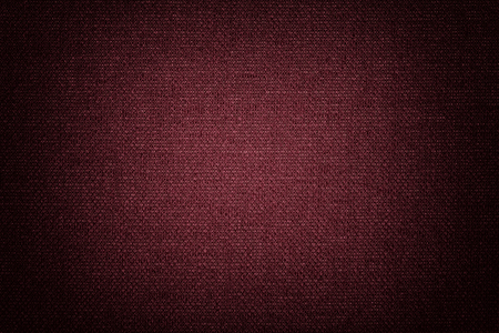 Dark red background from a textile material with wicker pattern, closeup. Structure of the wine fabric with texture. Cloth backdrop with vignette. Reklamní fotografie