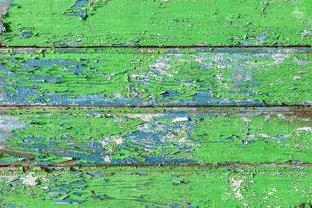 Texture of old green wooden wall with cracked paint. Structure of painted weathered vintage surface.