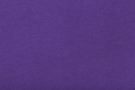 Dark purple matte background of suede fabric, closeup. Velvet texture of seamless violet woolen felt.