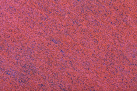 Structure of dark red background with blue spots of felt fabric, closeup. Texture of woolen matt textile. Cloth backdrop.