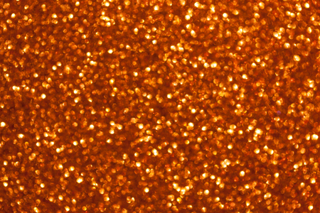 Blurred golden background with circle sparkling lights. Shiny orange glittery bokeh of christmas garland. Dark backdrop