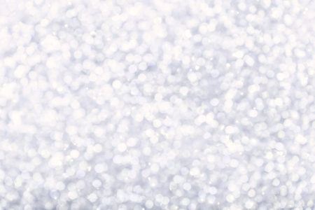 Blurred white background with circle sparkling lights. Shiny pastel silver glittery bokeh of christmas garland, snow. Holiday backdrop, snowflakes.