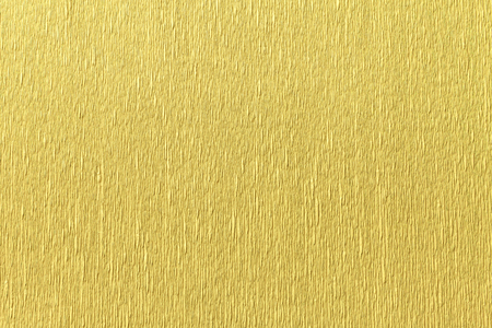 Textural of golden background of wavy corrugated paper, closeup. Structure of wrinkled crepe light yellow cardboard macro.