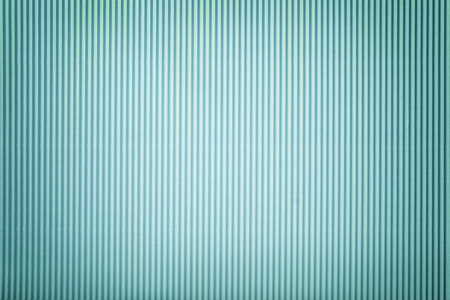 Texture of corrugated light blue paper with vignette, macro. Striped pattern of steel cardboard background, closeup.